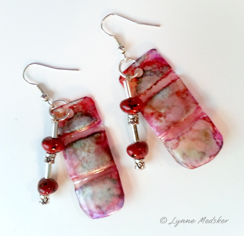 Earrings created from plastic drink bottle, old necklace parts and red stones, $15 pair © Lynne Medsker